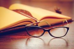 Notizbuch und Gläser auf einem Holztisch lizenzfreies stockbild