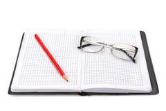 Notizbuch und Gläser lokalisiert auf Weiß Lizenzfreie Stockbilder