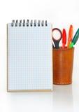 Notizbuch und Glas mit Bleistiften und Scheren. Lizenzfreies Stockfoto