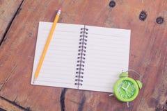 Notizbuch und grüne Uhr stockfoto