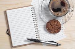Notizbuch und Kaffee mit Plätzchen Stockbild