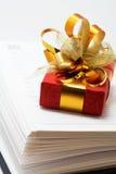 Notizbuch und rotes Geschenk Stockfotografie