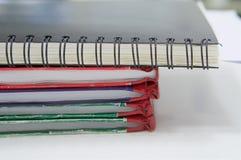Notizbuch und Stapel des Berichtsbuches im Raum lizenzfreies stockbild