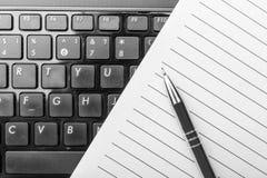 Notizbuch und Stift auf der Tastatur Stockbild