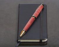 Notizbuch und Stift auf einem schwarzen Schreibtisch Stockbilder