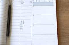Notizbuch und Stift auf Holztisch Lizenzfreie Stockfotografie