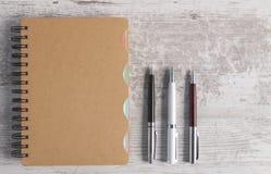 Notizbuch und Stift im hölzernen Hintergrund lizenzfreie stockfotos