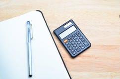 Notizbuch und Stift mit Taschenrechner auf Holztisch Lizenzfreie Stockfotos