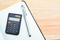 Notizbuch und Stift mit Taschenrechner auf Holztisch Stockfotografie
