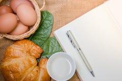 Notizbuch und Stift, setzten an Sackleinen mit Hörnchen und Eiern Lizenzfreie Stockbilder