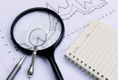 Notizbuch, Vergrößerungsglas, Stift und Finanzdiagramm, Geschäftsarbeitsnotfall Stockfotografie