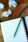 Notizbuch, zerknitterte Papiere und bunte Bleistifte Stockfotografie
