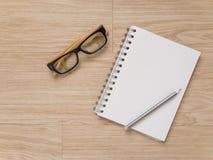 Notizbuchaugengläser und -bleistift auf Holzfußboden Lizenzfreie Stockbilder