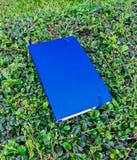 Notizbuchblau gesetzt auf grünes Gras Lizenzfreies Stockfoto