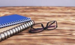 Notizbuchbuchgläser auf hölzernem Hintergrund lizenzfreie stockfotos