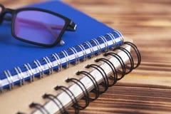 Notizbuchbuchgläser auf hölzernem Hintergrund lizenzfreies stockfoto