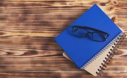 Notizbuchbuchgläser auf hölzernem Hintergrund lizenzfreie stockbilder
