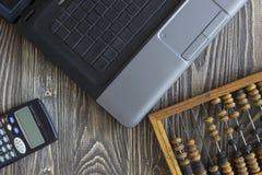 Notizbuchlaptoprechnungen und -taschenrechner, die auf einem Holztisch liegen Stockbilder