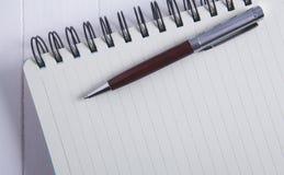 Notizbuchstift auf hölzernem Hintergrund stockfoto