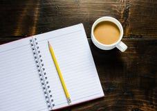 Notizbuchstift und -Tasse Kaffee in der hölzernen Tabelle Stockfotografie