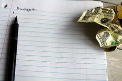 Notizbuchstiftdollar prägt Budgetplanung Stockbild