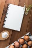 Notizbuchweiß auf einem Bretterboden mit Ei Lizenzfreie Stockfotos
