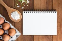 Notizbuchweiß auf einem Bretterboden mit Ei Stockfotografie