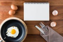 Notizbuchweiß auf einem Bretterboden mit Ei Stockfotos