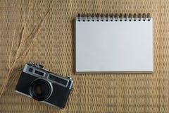 Notizbuchweiß auf einem Bretterboden mit einer Filmkamera Lizenzfreie Stockbilder