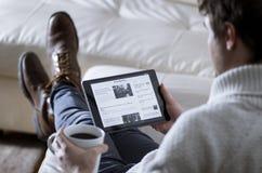 Notizie App della lettura dell'uomo sulla compressa Fotografia Stock Libera da Diritti