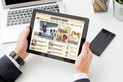 Notizie dal mondo degli affari della lettura dell'uomo d'affari sulla compressa Tutti i contenuti si compongono immagini stock