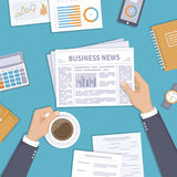 Notizie dal mondo degli affari Uomo d'affari che tiene una tazza di caffè e del giornale sul desktop Fotografie Stock Libere da Diritti