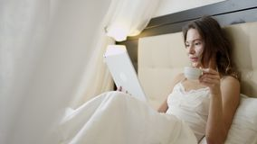 Notizie della lettura della donna sul suo pc della compressa mentre trovandosi a letto e sul caffè bevente stock footage