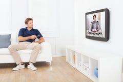 Notizie di sorveglianza dell'uomo sulla TV a casa Fotografia Stock