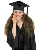 Notizie di sussurro sorridenti della ragazza dell'allievo di graduazione Immagine Stock