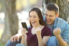 Notizie emozionanti della lettura delle coppie in un telefono Fotografia Stock Libera da Diritti