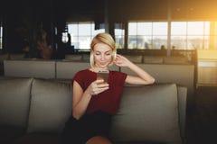 Notizie femminili splendide della lettura via la rete sul telefono cellulare mentre aspettando il suo ordine in caffetteria moder Fotografia Stock Libera da Diritti