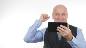 Notizie finanziarie di Use Tablet Read dell'uomo d'affari felice le buone fanno Victory Hand Gestures fotografia stock libera da diritti