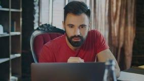 Notizie moderne della lettura dell'uomo di affari sul computer portatile in ufficio Sorriso del giovane stock footage