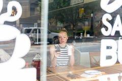 Notizie premurose della lettura della donna sul telefono cellulare durante il resto in caffetteria immagini stock libere da diritti
