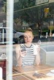 Notizie premurose della lettura della donna sul telefono cellulare durante il resto in caffetteria immagini stock
