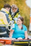 Notmediziner, die Kopfverletzung der verletzten Frau kleiden Lizenzfreie Stockfotografie