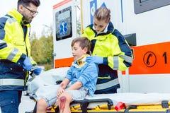 Notmediziner, die um verletztem Jungen sich kümmern Stockfotos