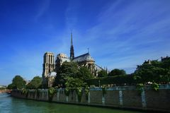 Notre Dame basilica in Paris. Also known as Notre-Dame de Paris on spring blue sky and grenn trees Stock Images