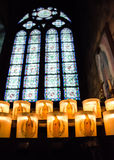 Notre Dame Cathedral Candles. Burning in the cathedral with stain glass window in background Stock Images