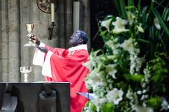 Notre Dame Cathedral Catholic Mass. A prist lifts a goblet to the attendees of a catholic mass taking place in the notre dame cathedral in paris Stock Image