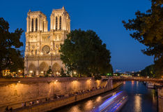 Notre Dame cathedral at dusk with blurred boat lights over Seine Royalty Free Stock Photos