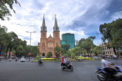 Notre Dame cathedral. HCMC, VIETNAM-JAN. 9 2014: Motorbike passing the Notre Dame cathedral in Ho Chi Minh City during rush hour Stock Photo