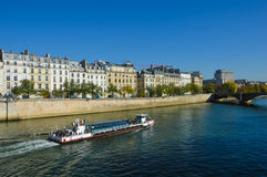 Notre Dame cathedral next to the river of Paris with boats and buildings summertime. Autumn Stock Photos