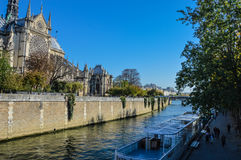 Notre Dame cathedral next to the river of Paris with boats and buildings summertime. River of Paris with boats and buildings summertime, France with the Royalty Free Stock Photos